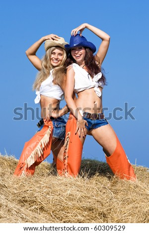 Two attractive girls on haystack. Young women in costumes of cowboys smiling and looking at camera