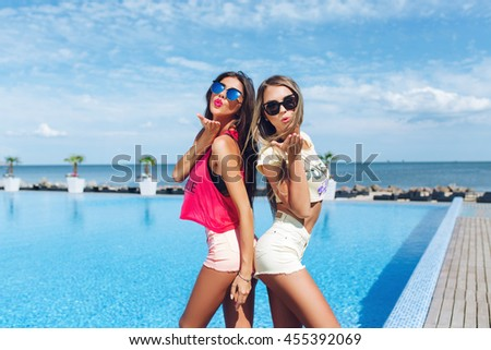 Two attractive girls with long hair in sunglasses are posing near pool on the sun. Brunette girl wears short pink shorts and T-shirt, blond wears yellow shorts and T-shirt. They standing back to back. - stock photo