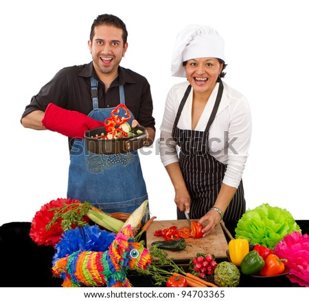 Two attractive happy chefs preparing for a Mexican celebration by cutting vegetables and flipping them in a frying pan.
