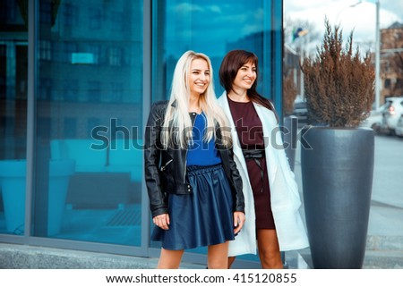 two attractive happy ladies brunette and blonde looking away and smiling outdoors - stock photo