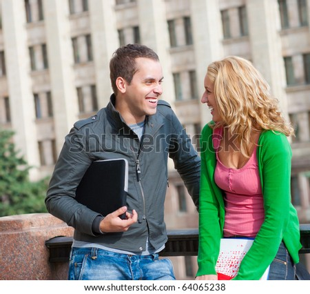 Two attractive happy students talking at campus - stock photo