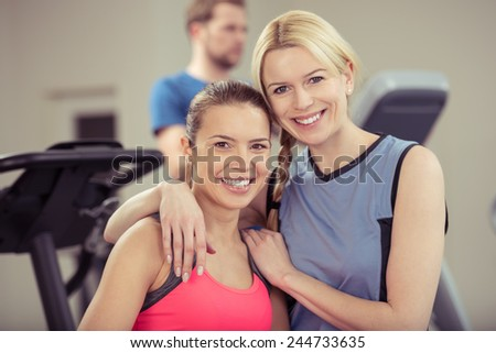 Two attractive healthy woman in a gym posing arm in arm smiling at the camera in a healthy lifestyle and fitness concept - stock photo