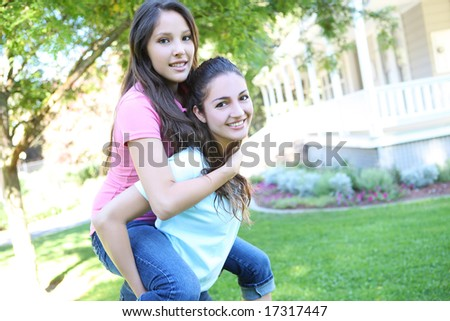 Two attractive hispanic sisters displaying the love of family at home - stock photo
