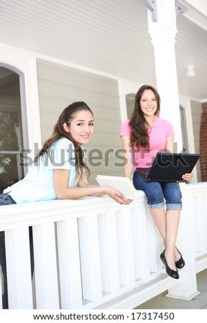 Two attractive hispanic sisters studying at home on the porch - stock photo
