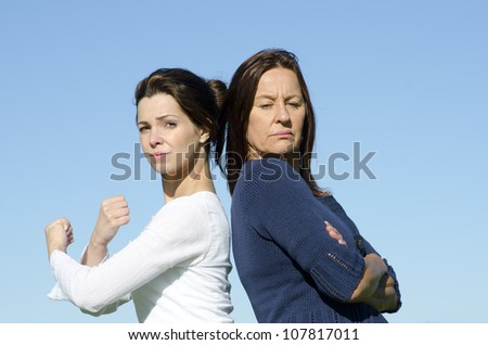 Two attractive looking women, two generations, mother and daughter, standing back to back, with determined respectively stubborn expression and with clear blue sky as background and copy space. - stock photo