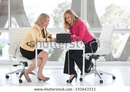 Two attractive mature women  sharing ideas on a touch pad in a penthouse - stock photo