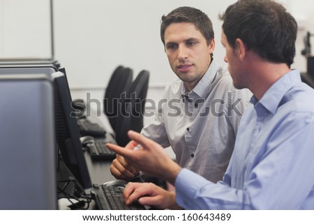 Two attractive men talking in computer class pointing at monitor - stock photo