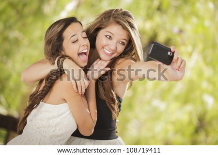 Two Attractive Mixed Race Girlfriends Taking Self Portrait with Their Phone Camera Outdoors. - stock photo