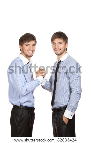Two attractive positive smile young business people brother twins standing shake hands, dressed in shirt, tie. Concept Success, Brotherhood, Unity, partnership, isolated over white background