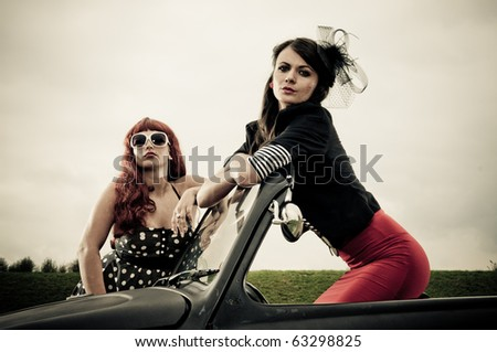 Two attractive retro 50s style dressed girls posing on car - stock photo