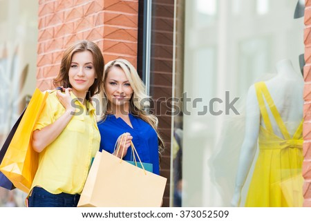 Two attractive sexy shopaholics posing near store window with yellow dress. - stock photo