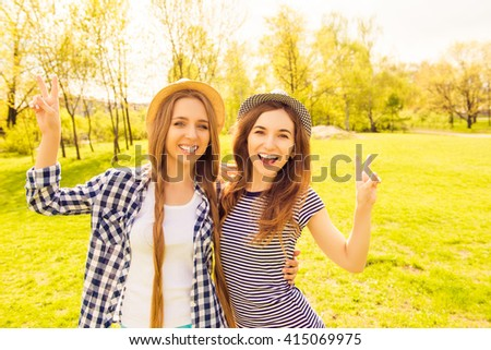Two attractive sisters in hats having fun and gesturing with two fingers - stock photo