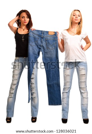 Two attractive slender trendy girls in the latest ragged designer jeans holding up an outmoded pair of blue denim jeans isolated on white - stock photo