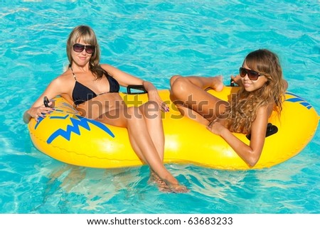 Two attractive slim and tanned young ladies lying on inflatable ring on sunny swimming pool on vacation or holiday - stock photo