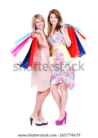 Two attractive smiling woman with multicolor shopping bags standing on a white background. - stock photo