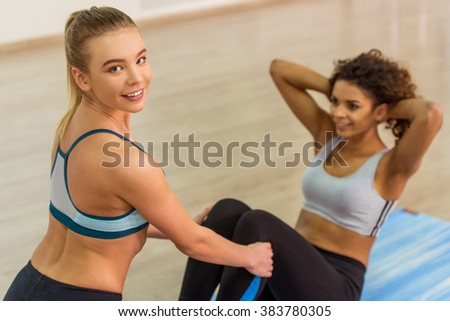 Two attractive sport girls smiling while working out and doing abs in fitness class. Beautiful blonde girl looking at camera - stock photo
