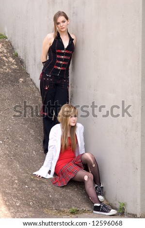 Two attractive teen girls model by a concrete wall, punk and emo fashions.