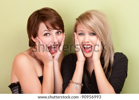 Two attractive teen girls scream towards the camera in front of a green wall.