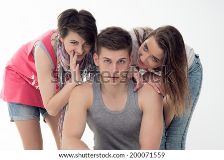 Two attractive teen girls whispering something with laughter to a cute handsome teen boy. Isolated on white background. Concept of love, youth, friendship, rumors - stock photo