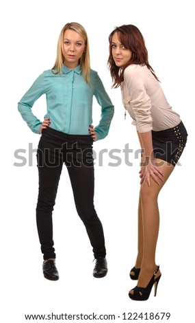 Two attractive teenage girls isolated on a white background standing having a friendly confidential conversation - stock photo