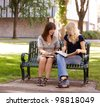Two attractive university students study together on a bench - stock photo