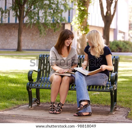 Two attractive university students study together on a bench