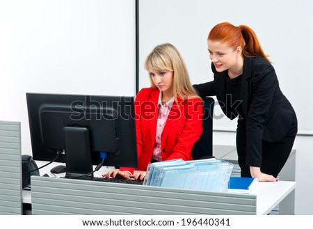 two attractive woman colleague workers in office working in computer