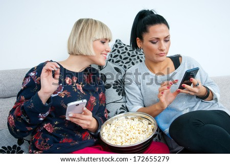 two attractive woman friends with mobile phones and popcorn on the sofa chating