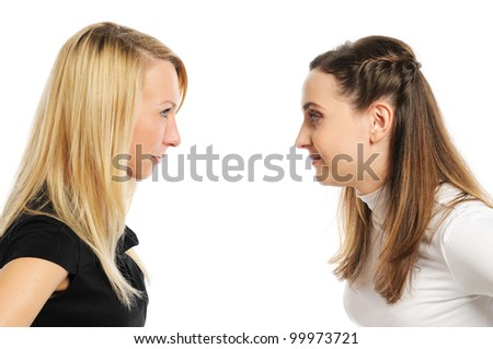 Two attractive women attentively look at each other. Isolated on white. - stock photo