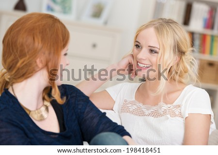 Two attractive women chatting as they relax at home sitting on a comfortable sofa in the living room laughing and smiling - stock photo