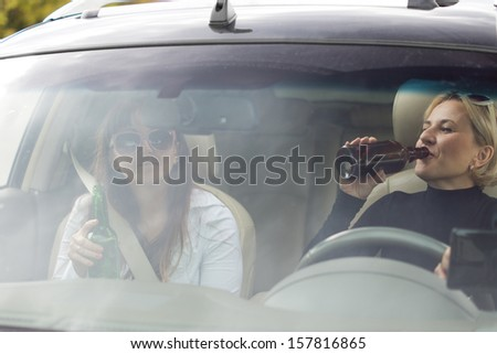 Two attractive women drinking alcohol from bottles while driving a car and posing a danger to other motorists, view through the front windscreen - stock photo