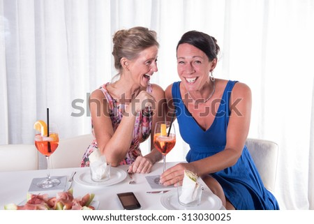 two attractive women giggling together