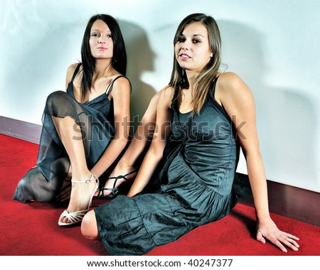 Two attractive women in black dresses, heels and with long hairs