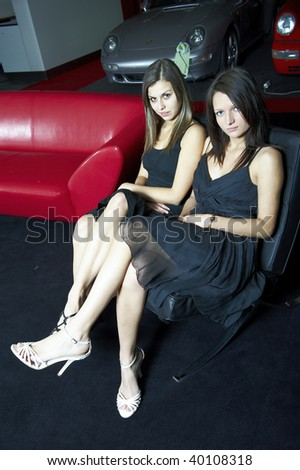Two attractive women in black dresses, heels and with long hairs on black sofa