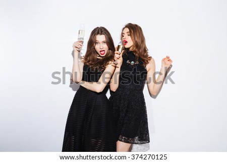 Two attractive women in night dress drinking champagne isolated on a white background - stock photo