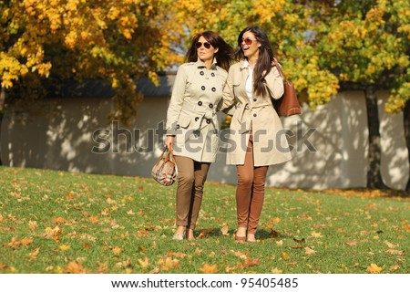 two attractive women in park at fall outdoors - stock photo