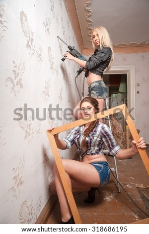 Two attractive women with puncher and picture frame do reconstruction in room - stock photo