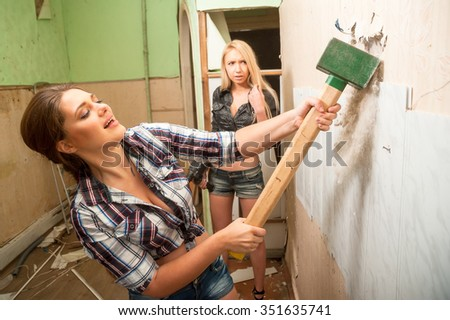 Two attractive women with sledge hammer and puncher making home improvement - stock photo