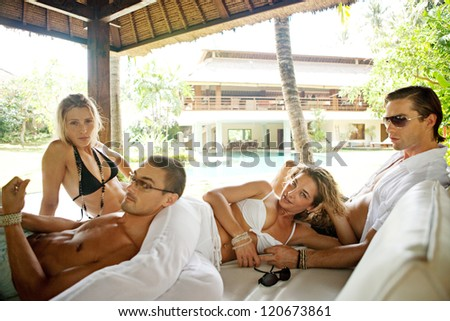Two attractive young couples lounging on an outdoors exotic bed in a luxury hotel at a tropical destination while on vacations.