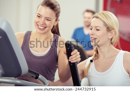 Two attractive young female friends working out in a gym smiling happily as they check the readout on the equipment after a workout - stock photo