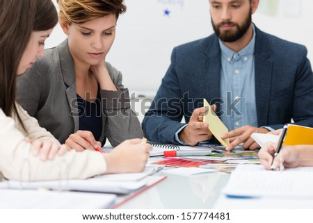 Two attractive young females business colleagues in a meeting having a discussion watched by a male coworker - stock photo