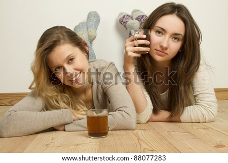 Two attractive young friends lying on the floor of the house and drink tea