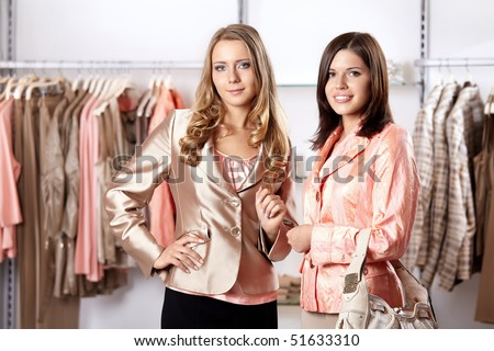Two attractive young girls against clothes in shop - stock photo