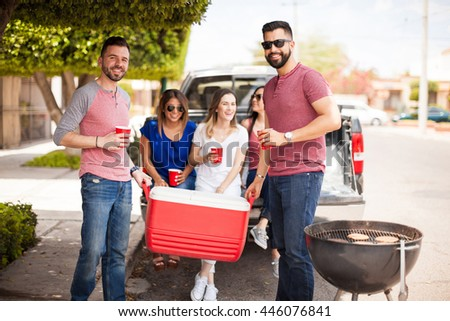 Two attractive young men carrying a cooler full of drinks for a barbecue with friends outdoors