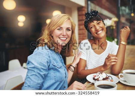 Two attractive young multiethnic female friends enjoying coffee and cake together in a cafeteria smiling happily at the camera as they sit together at a table - stock photo