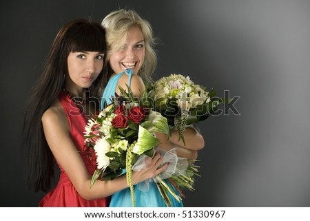 Two attractive young pretty girls with bunches of flowers. - stock photo