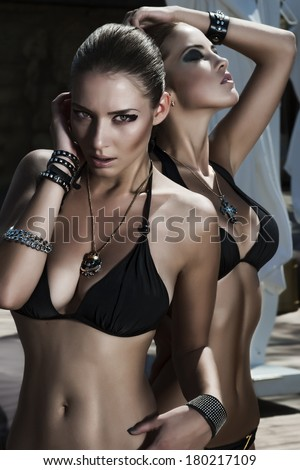 two attractive young sexy and beautiful women in black bikini by the pool. rock style - stock photo