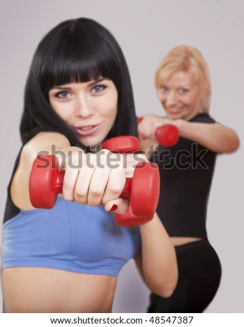 Two attractive young women are punching with hand weights over gray background
