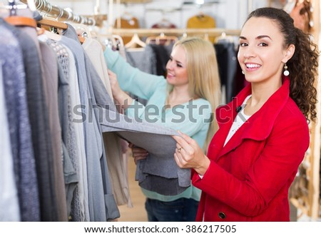 Two attractive young women choosing basic garments at clothing store