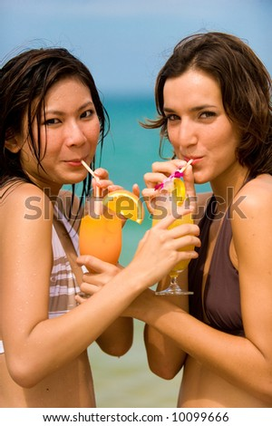 Two attractive young women drinking cocktails on beach